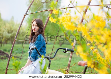 Week end in spring park. Attractive young brunette woman with a bicycle against nature background. - stock photo