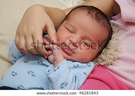 Week Old Newborn Infant dressed in blue long sleeve shirt making face - stock photo