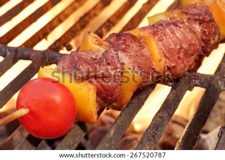 Weekend BBQ Meat Beef  Kebab Or Kabob On The Hot Flaming Grill. Flames of Fire on The Background. Summer Party or Picnic Food. - stock photo