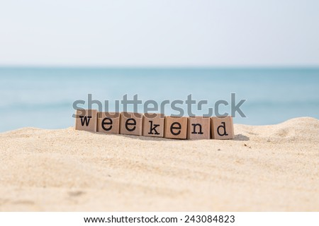 Weekend word on wood rubber stamps stack on the sand beach for vacation and summer season concept, beautiful ocean view during daytime on a sunny day with blue sky on background - stock photo