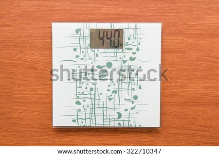 Weighed scale digital show 44 kg. It on wood floor. - stock photo