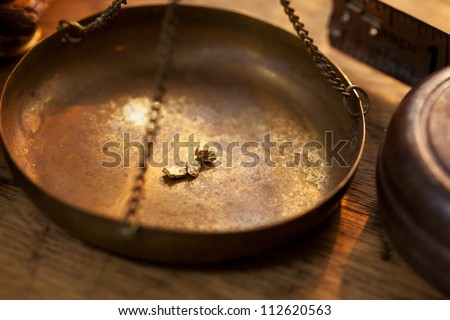 Weighing a gold nugget on a old brass scale dish for trade or exchange. - stock photo