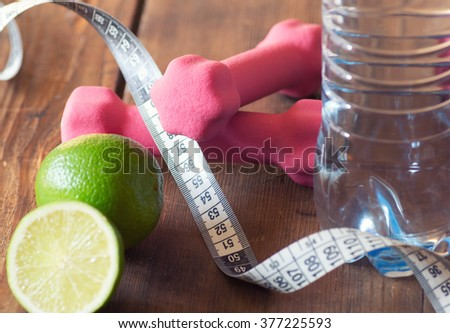 weight loss concept with tape measure organic lime, pink dumbbells and natural bottle of water - stock photo