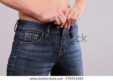 Weight loss, Get fit again concept. Slim woman zipping up a tight pair of jeans close up. Young Mother Wear Her Pre-Pregnancy Jeans - stock photo