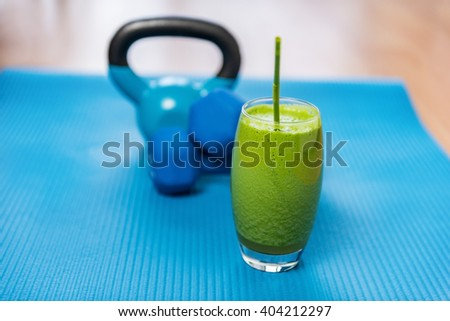 Weight loss healthy eating green vegetable smoothie with free weights kettlebells and exercise mat in gym center. Health and fitness concept. Vegetarian diet and nutrition for strength training. - stock photo
