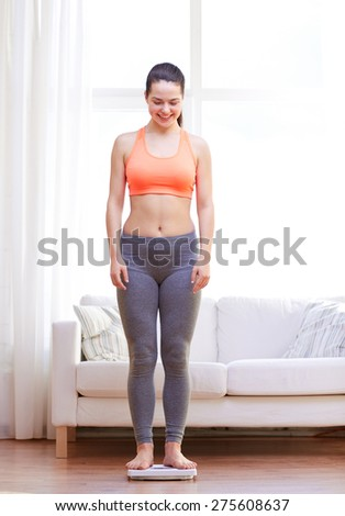 weight loss, slimming, healthy lifestyle and people concept - happy young woman weighing herself on scales at home - stock photo