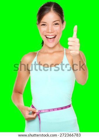 weight loss woman smiling happy excited standing with measuring tape giving thumbs up success hand sign isolated cutout on green chroma key background. Asian female fitness model. - stock photo