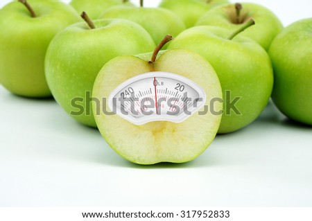 Weight scale made of green apple isolated on white background - stock photo