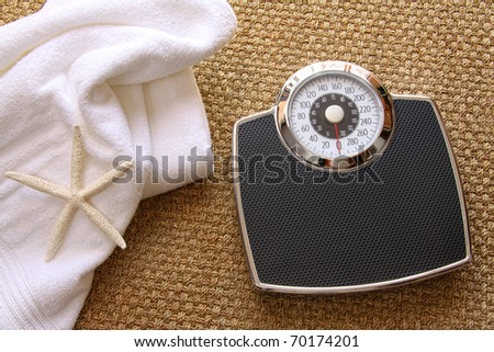 Weight scale with white towel on seagrass carpet - stock photo