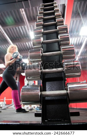 Weight training equipment, vertical stand with steel dumbbells in sports club - stock photo