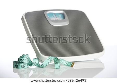 Weighting scales with a measuring tape on white background. - stock photo