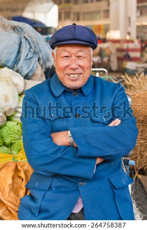 WEIHAI-DEC. 1, 2006. Traditionally dressed Farmer on a market. According Academy of Social Science 40 to 50 million farmers are landless. Rural pension is 12,000 yuan, urban pension 33,000 yuan a year - stock photo