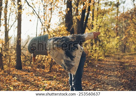 Weird man in a creepy rubber pigeon bird mask in the autumn sunset forest - stock photo
