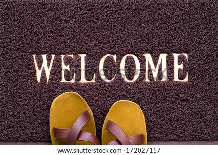 Welcome carpet with beach shales on it - stock photo