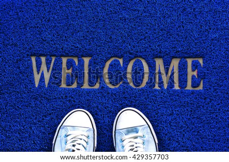 Welcome carpet with shoes on it. - stock photo
