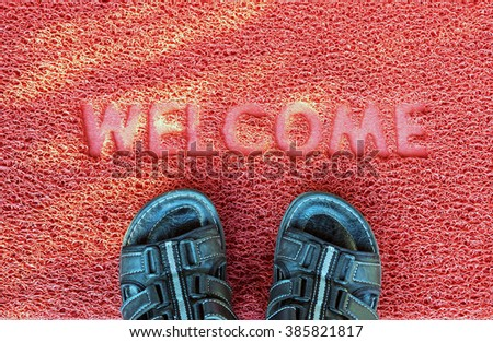 Welcome door capet  with foot ware on it. - stock photo