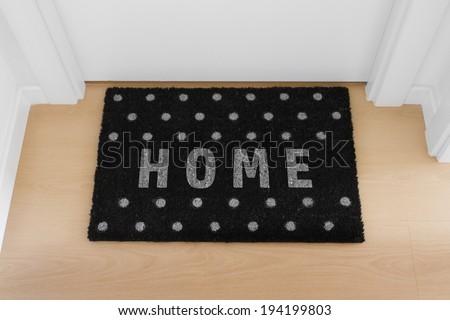 Welcome home black doormat with close door - stock photo