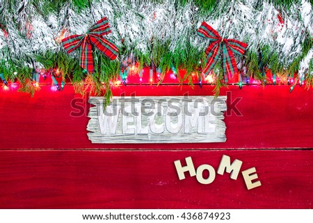 Welcome Home sign hanging by snowy green Christmas tree garland border with plaid bows and lights on antique rustic red wood background - stock photo