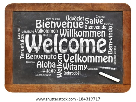 Welcome in different languages - a word cloud in white chalk text on a vintage slate blackboard isolated on white - stock photo