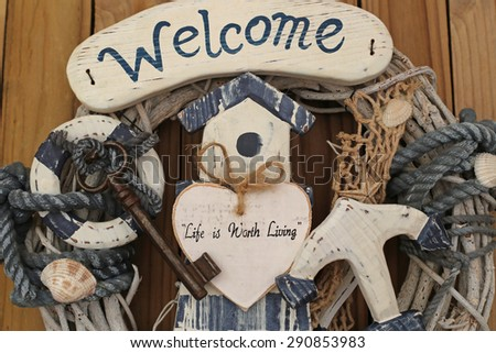 Welcome - Life is Worth Living - text on a decorative white wooden heart on maritime background, lighthouse, life buoy, door key, net, shells, marine rope, anchor, dry branches, close up, top view - stock photo