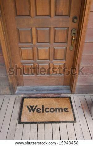 Welcome mat on a wooden deck by front door - stock photo