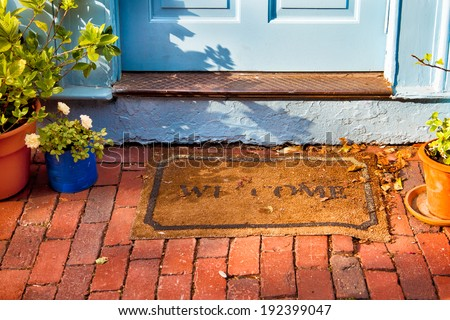 Welcome mat outside a cottage front door.  - stock photo