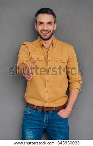 Welcome on board! Cheerful mature man stretching out hand for shaking while standing against grey background - stock photo