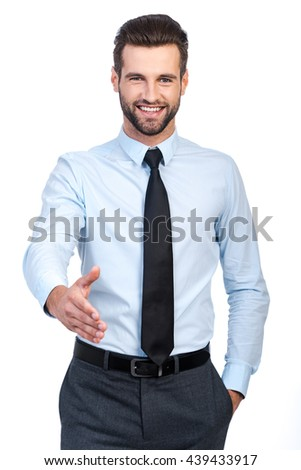 Welcome on board! Confident young handsome man in shirt and tie stretching out hand for shaking and smiling while standing against white background  - stock photo