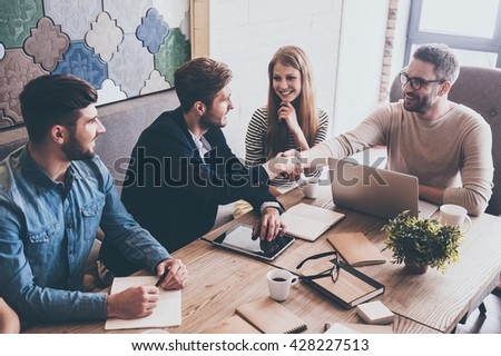 Welcome on board! Top view of two men shaking hands and looking at each other with smile while sitting at the business meeting with their coworkers - stock photo
