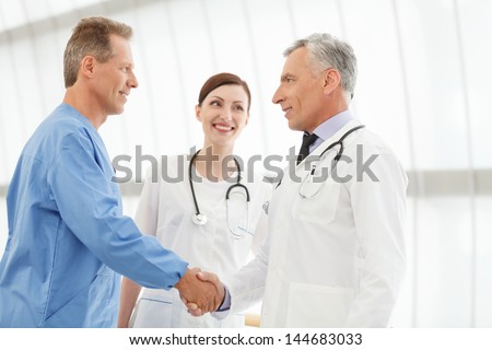 Welcome on board! Two mature doctors handshaking while  beautiful young nurse looking at them - stock photo