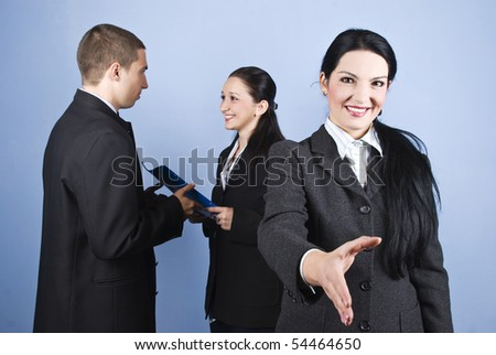 Welcome or joined in business with a business woman who standing with hand open and others persons standing in background give each other a folder with contract - stock photo