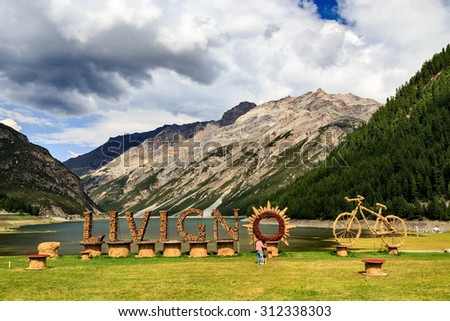 Welcome Sign for Village of Livigno with Bicycle Sculpture on Shores of Picturesque Lake in Valley Surrounded by Italian Alps Under Cloudy Sky - stock photo
