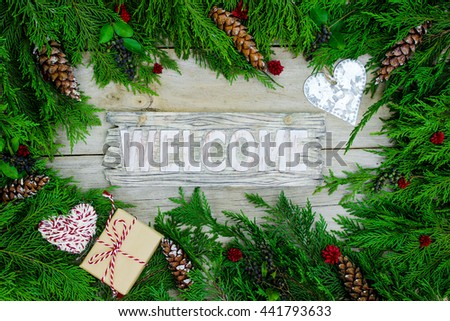 Welcome sign hanging by green Christmas tree garland, rope heart, brown paper package tied up in string and tin heart border on antique rustic wood background - stock photo