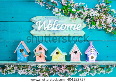 Welcome sign hanging over colorful birdhouses with butterfly on shelf by spring tree flowers on antique rustic teal blue wood background; pink, purple, yellow, orange birdhouses - stock photo