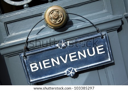 Welcome sign on a door of a French hotel - stock photo
