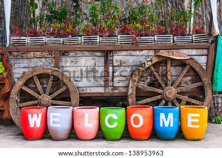 Welcome sign on colorful pottery - stock photo