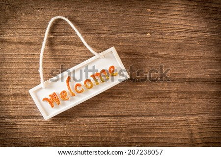 Welcome sign on wooden fence - stock photo