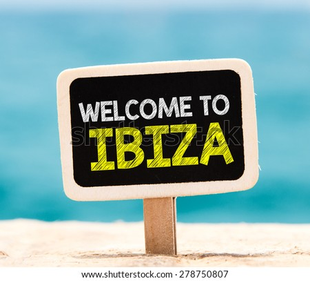 Welcome to Ibiza on chalkboard. Welcome to Ibiza text written on chalkboard, on beach - stock photo