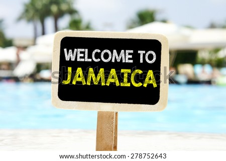 Welcome to Jamaica on chalkboard. Welcome to Jamaica text written on chalkboard near pool - stock photo