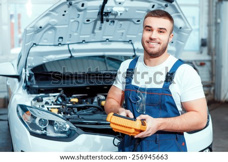 Welcome to our service station. Portrait of a smiling handsome mechanic in uniform posing by the car at car service station holding electronic repair tools - stock photo