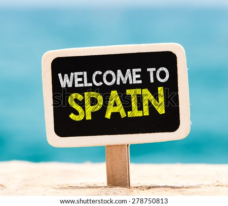 Welcome to Spain on chalkboard. Welcome to Spain text written on chalkboard, on beach - stock photo