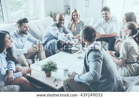 Welcome to team! Group of confident business people sitting around the desk together while two men shaking hands and smiling - stock photo