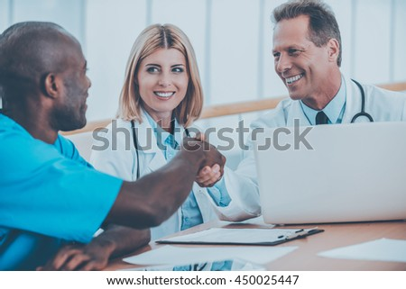 Welcome to team! Two cheerful doctors shaking hands while sitting together with female doctor - stock photo