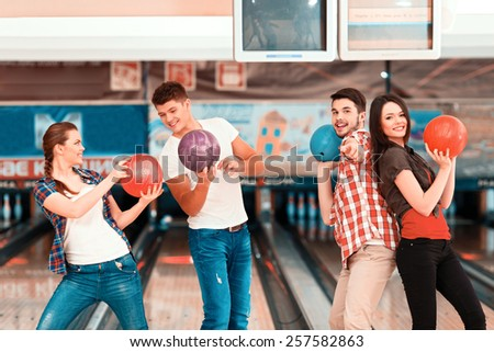Welcome to the bowling club. Beautiful young people holding bowling balls and posing against bowling alleys - stock photo