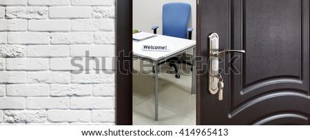 Welcome to the office. Half opened door to office. Door handle, door lock. Opening door. Privacy, safety concept. Entrance to the office workplace. Door at white brick wall, modern interior design.  - stock photo