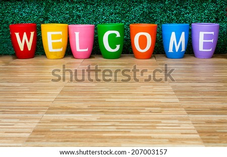 Welcome word separate alphabet one by one on ceramic pot. - stock photo