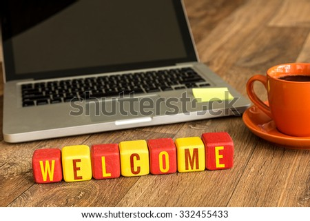 Welcome written on a wooden cube in front of a laptop - stock photo