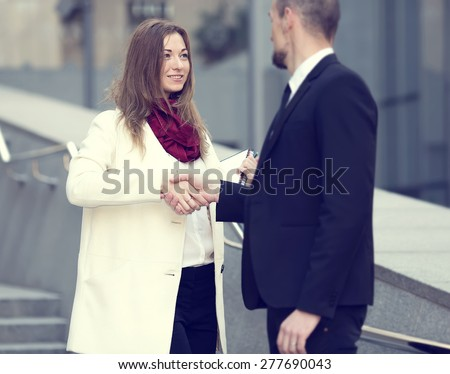Welcoming business woman giving a handshake. Business contract. Business people. Business meeting. Meet the client. Business communication between man and woman. Business woman the focus of attention. - stock photo