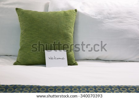 Welcoming hotel bed with pillows and welcome card close up. - stock photo