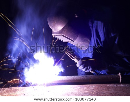 Welder and bright sparks. Construction and production - stock photo